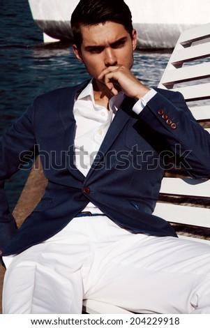 Handsome business man near yacht - stock photo