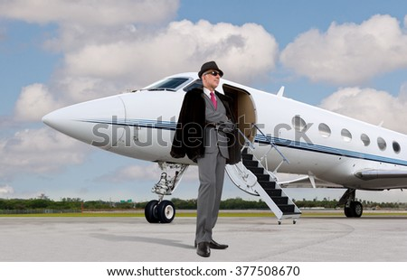 Handsome business man on the steps of a private jet wearing a hat