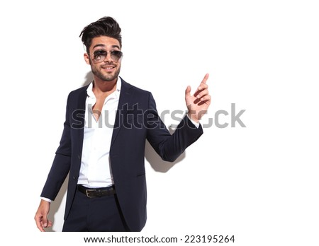 Handsome business man pointing at something to his left, looking away from the camera, against a white wall - stock photo