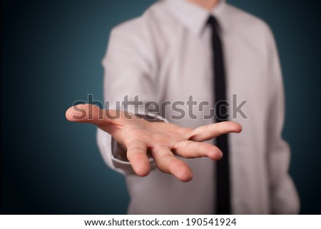Handsome business man presenting with hand empty copy space - stock photo