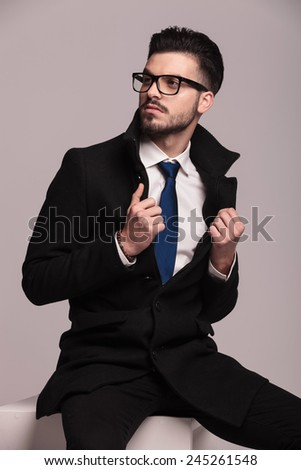 Handsome business man sitting while pulling his collar. He is looking away from the camera. - stock photo