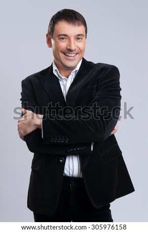 handsome business man smiling isolated on gray background - stock photo