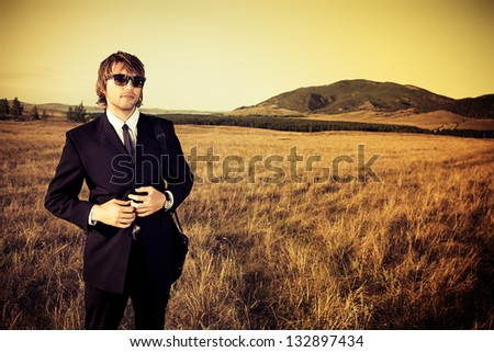 Handsome business man standing in a field with a feeling of freedom.