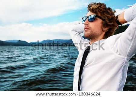 Handsome business man standing on a seaside and looking into the distance. - stock photo