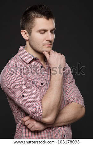 Handsome business man standing with folded hands with eyes closed against black background