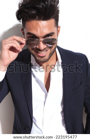 Handsome business man taking of his sunglasses, looking at the camera, against a white wall