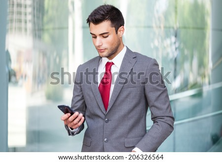 Handsome business man using a cell phone - stock photo