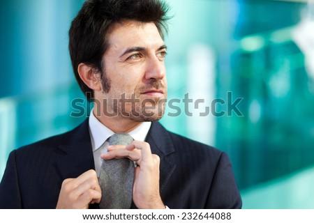 Handsome businessman adjusting his tie - stock photo