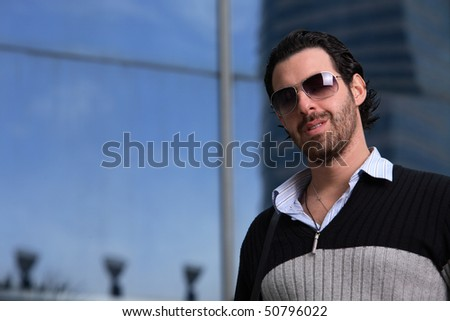 Handsome businessman against his office building
