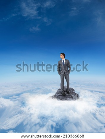 Handsome businessman against mountain peak through the clouds