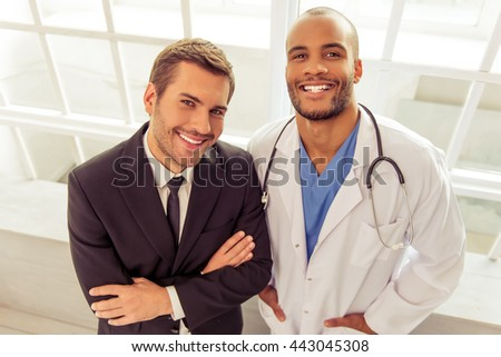 Handsome businessman and Afro American doctor are looking at camera and smiling, standing in hospital - stock photo