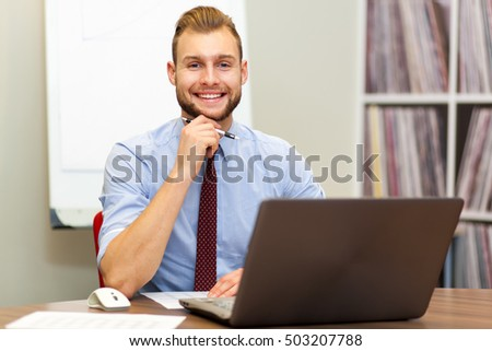 Handsome businessman at his desk in the office