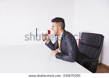 Handsome businessman at his office screaming over the megaphone - stock photo