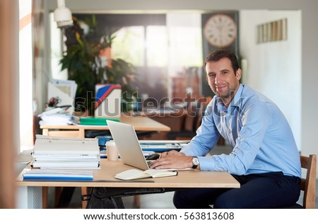 Handsome businessman at work on a laptop in an office