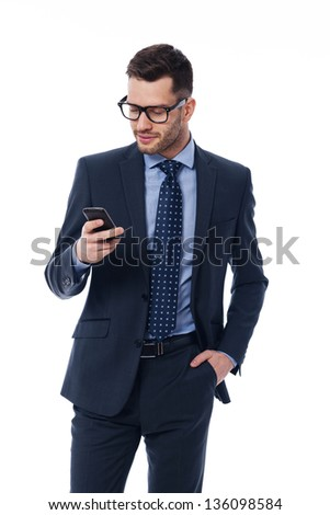Handsome businessman checking emails on the phone - stock photo