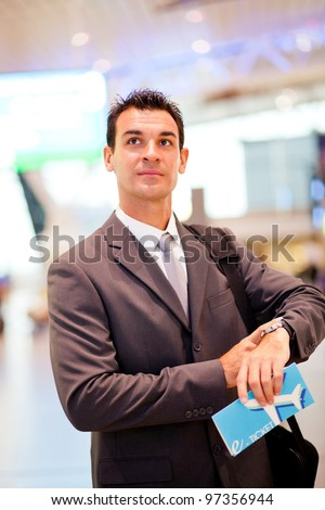 handsome businessman checking flight departure time at airport - stock photo