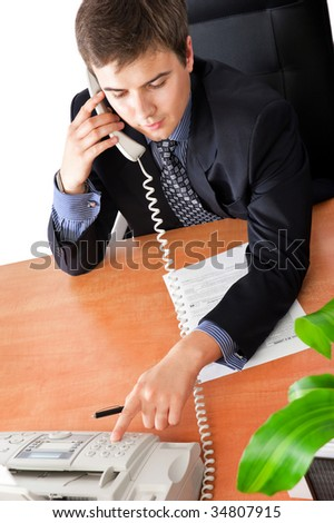 Handsome businessman dialing on the phone in an office environment - stock photo
