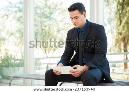 Handsome businessman doing some work on a tablet computer while sitting on a bench - stock photo