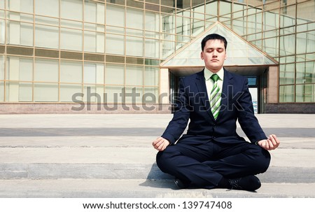 Handsome businessman doing yoga near building office - stock photo