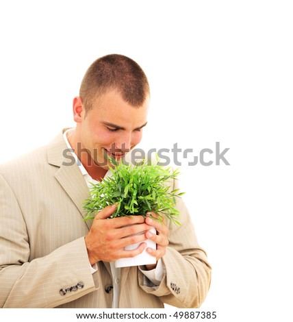 Handsome businessman enjoying his plant isolated on white - stock photo