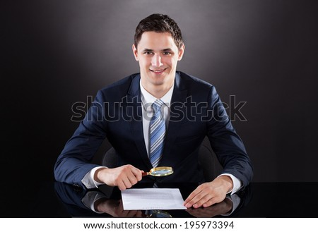 Handsome businessman examining contract paper with magnifying glass at desk against black background