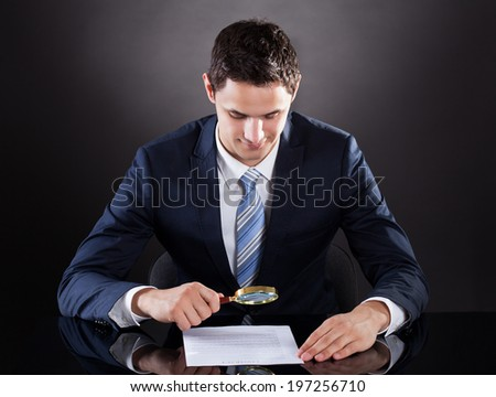 Handsome businessman examining contract paper with magnifying glass at desk against black background - stock photo