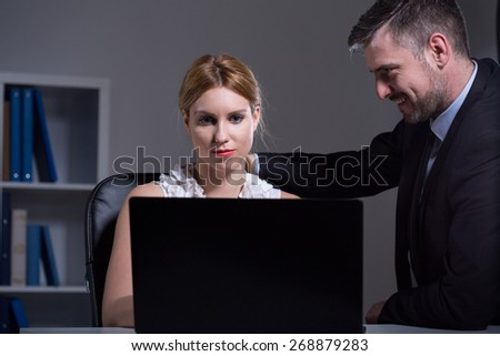 Handsome businessman flirting with young beautiful secretary
