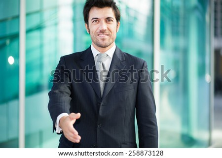 Handsome businessman giving you his hand - stock photo