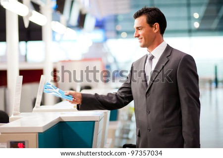 handsome businessman handing over air ticket at airline check in counter