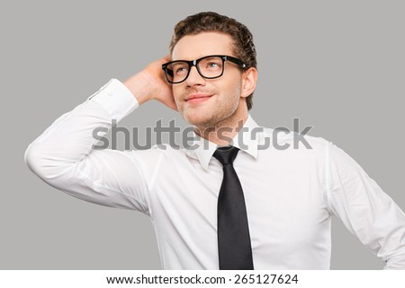 Handsome businessman. Handsome young man in shirt and tie touching his head and smiling while standing against grey background