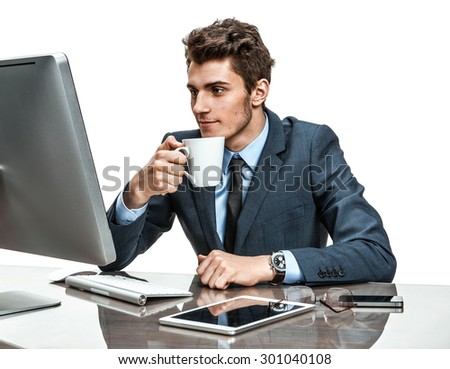 Handsome businessman having a coffee-break in office sitting at the table / photos of modern businessman at the workplace - stock photo