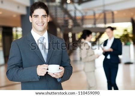 handsome businessman having coffee break in office - stock photo