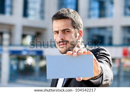 Handsome businessman holding blank business card, outdoor