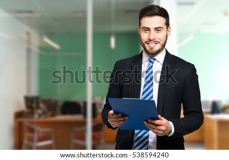 Handsome businessman holding documents in his office