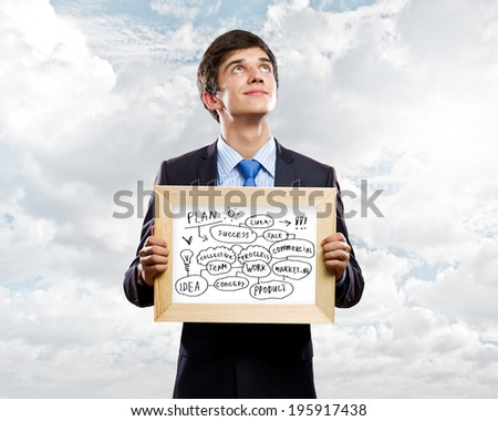 Handsome businessman holding frame with business sketches