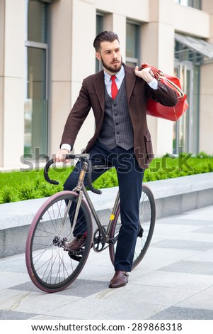 Handsome businessman in a jacket with red bag sitting on  his bicycle on city streets. The concept of the modern lifestyle of young men - stock photo
