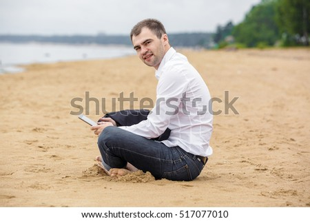 Handsome businessman in a suit and a white shirt works on the tablet sitting on the sand. His jacket lay on his knees. He is without shoes. A man looks into the camera.