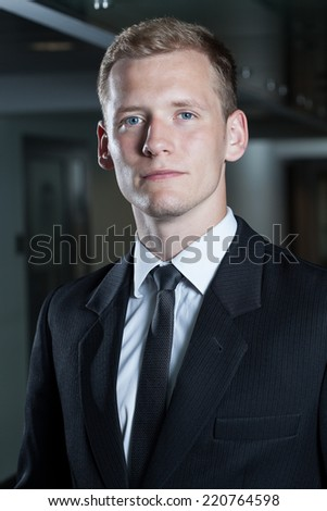 Handsome businessman in a suit standing in a hallway. - stock photo