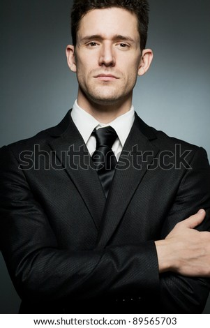 Handsome businessman in black suit expressing confidence.