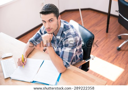 Handsome businessman in casual cloth signing document in office and looking at camera - stock photo