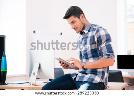 Handsome businessman in casual cloth using tablet computer in office - stock photo