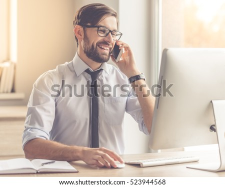 Handsome businessman in eyeglasses is using a computer, talking on the mobile phone and smiling while working in office