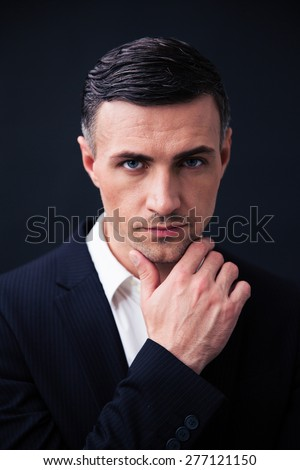 Handsome businessman in formal wear looking at camera over black background - stock photo