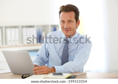 Handsome businessman in office working on laptop