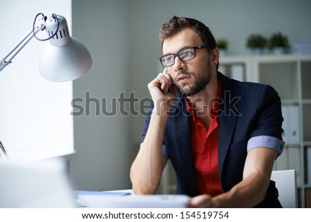Handsome businessman in smart casual and eyeglasses speaking on the phone in office - stock photo