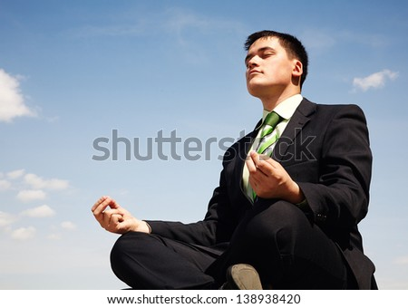 Handsome businessman in suit doing yoga - stock photo