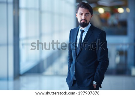 Handsome businessman in suit looking at camera in office - stock photo