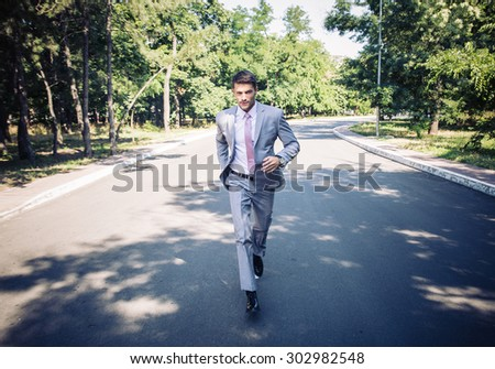 Handsome businessman in suit running in park - stock photo