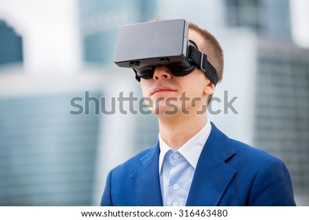 Handsome businessman in suit standing at the street with head-mounted display on. Modern skyscrapers on the background.  - stock photo