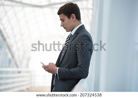 Handsome businessman in suit using smartphone in office - stock photo